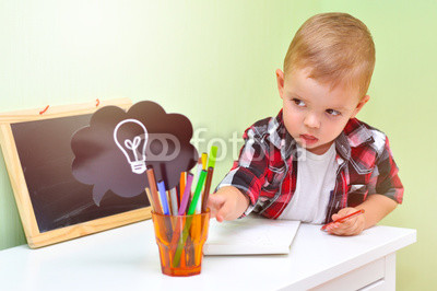 "Foto obraz na płótnie canvas trzyczęściowy - ""tryptyk"" - A cloud with a lightbulb symbolizing an idea or a thought. A glass with colored pencils and markers. A two-year-old baby boy in a red checkered shirt sits at a table and reaches out to the idea."